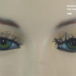 Poziome zdjęcie przedstawiające parę oczu kobiecego manekina. Brązowe brwi, zielone tęczówki i rzęsy, z czego ta po prawej stronie jest prawie odklejona od oka.